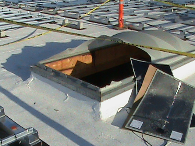 A skylight is raised slightly from a white rooftop and half the plastic covering is broken. There are jagged edges where the covering has broken and flat, black, flexible solar panels are placed on the roof near the opening.