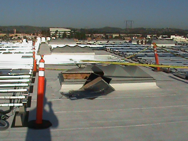 Yellow incident scene tape blocks off a broken skylight with two flexible black solar panels placed against it. There are metal rods on the surrounding rooftop where solar planels are meant to be placed.