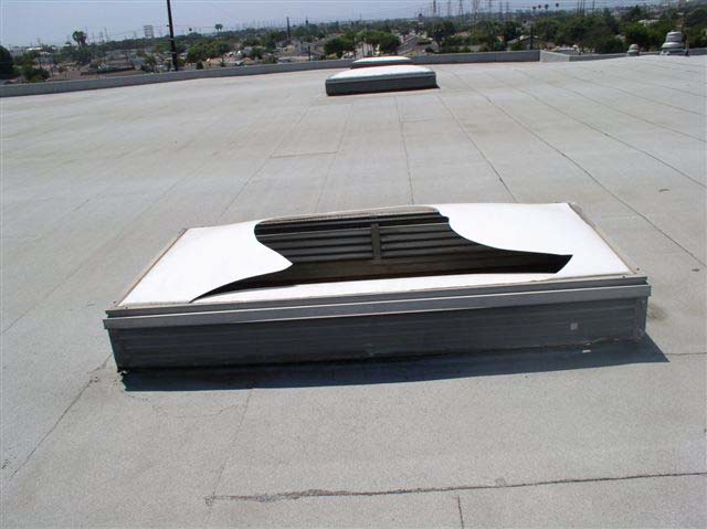 A skylight on a white rooftop. The covering is broken unevenly with jagged edges.