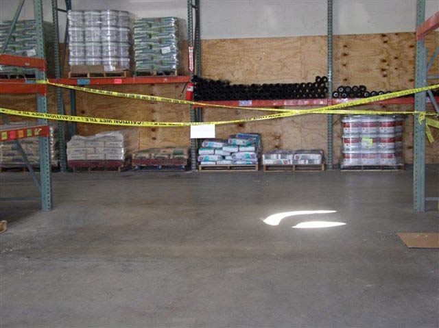 Yellow tape is tied across two large shelving units in a warehouse to block access to an area. There are bags, pipes, boxes, and tubs stacked in pallets against the wall behind the roped-off area.