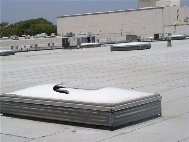 A broken skylight is on a white rooftop. In the distance are more skylights and a rooftop air conditioning unit.
