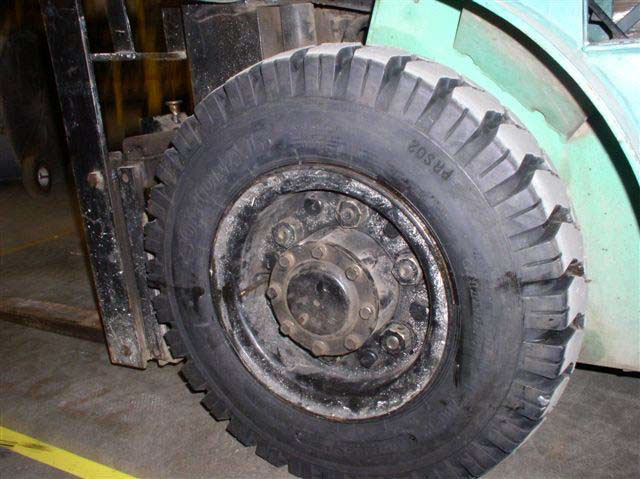 A close-up of a large, black tire with heavy tread and a black metal rim with six lug nuts and a large center cap with eight lug nuts.