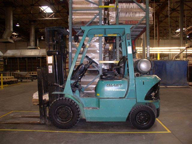 A blue-green forklift is parked in front of a tall shelving unit inside a warehouse. The front wheels are larger in diameter than the rear wheels.