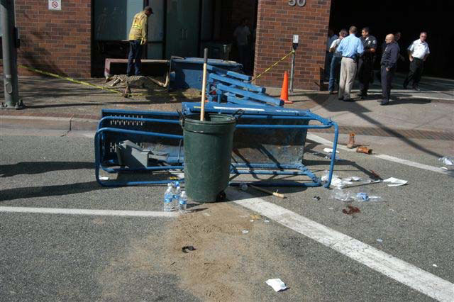 An upright garbage pail stands in front of the platform of the toppled lift. Blood and dirt are on the street next to the platform.