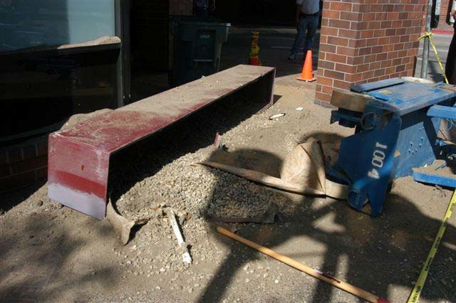 A dark red and wide planter box lies on its side on a concrete sidewalk with rocks and soil spilled over a wide area.