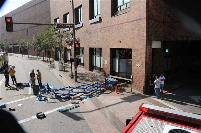 The fallen lift lies across a sidewalk and street beneath a window with a missing planter box underneath of it.