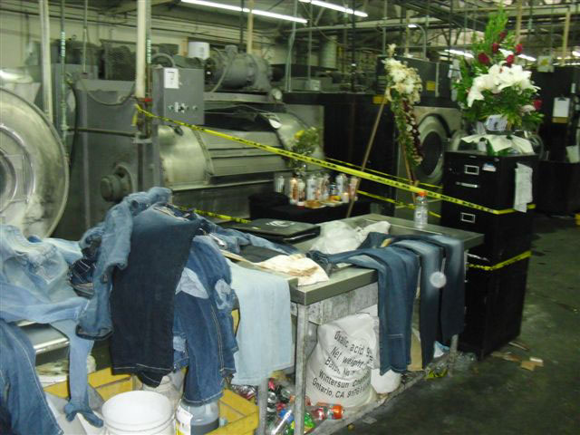 Denim clothing is piled on a work table near a large metal washing machine that is surrounded by yellow tape. Flowers are set on a filing cabinet nearby and a large floral wreath is in front of the machine where the worker died.