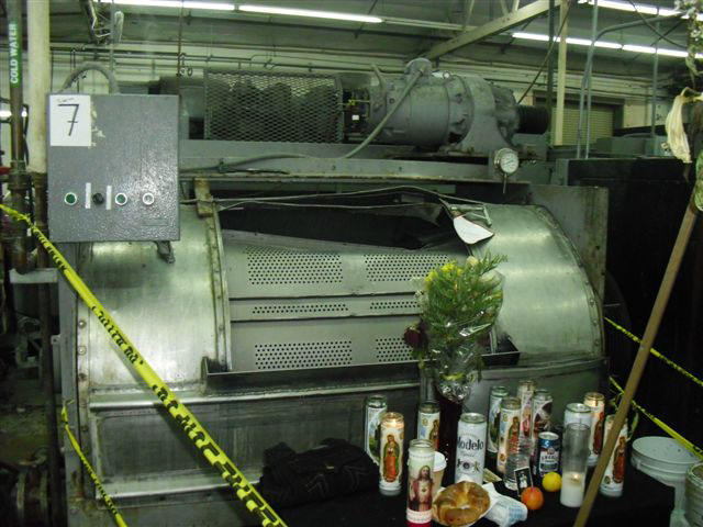 Candles and flowers sit on a table in front of the damaged metal industrial washing machine where the worker died. The machine has a damaged, bent semi-cylindrical sliding vented door opening where the worker became trapped.