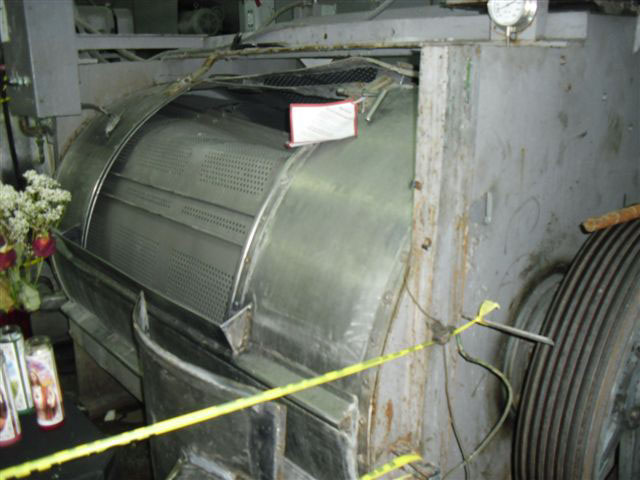 Close-up of the metal industrial washing machine with a large dent on top where colleagues tried to pull the trapped worker out of the machine. The machine is encased in metal with sharp corners.
