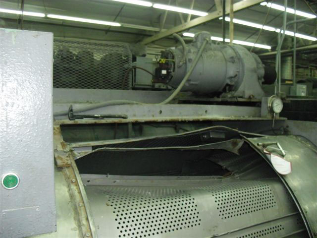 Close-up of opening of machine with a large dent and bent metal on top where workers tried to pull the trapped worker out of the opening.