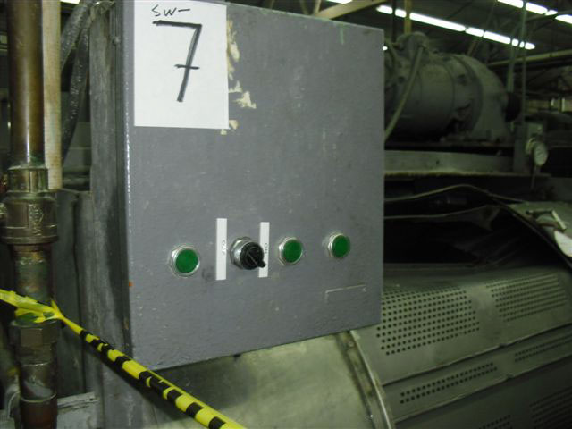 Close-up of the control panel in a metal box with a row of three green buttons and one black switch. There is a large paper taped on the top with a handwritten 7.