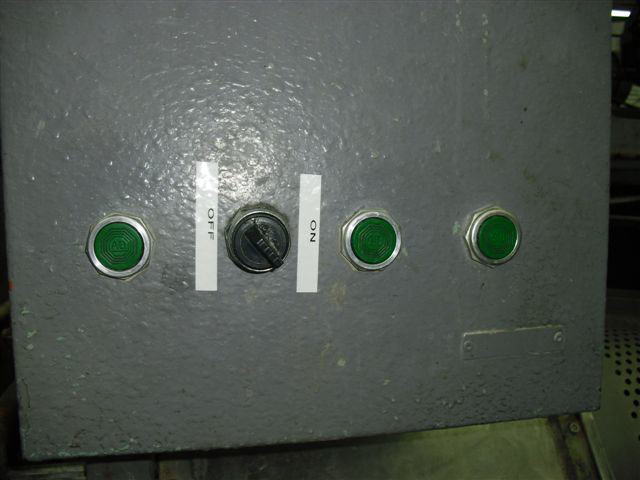 Closeup of horizontal control row with unlabeled green button on the left next to a black switch with an off label to the left and an on label to the right. There are two unlabeled green buttons to the right of the switch.