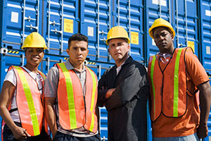 Dock workers standing in front of containers outside