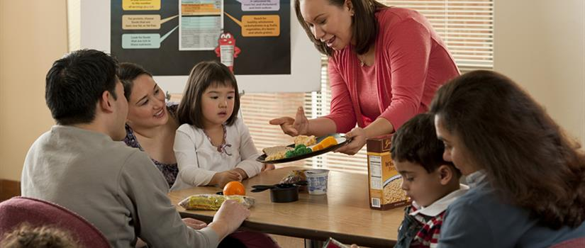 Nutritionalist presenting a well-portioned plate to a small group in a classroom setting